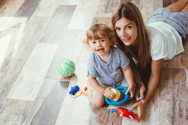 Mamma och son leker på ett nyslipat golv